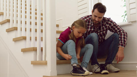 Father helping her daughter to wear shoes on stairs in a comfortable home 4k Live Action
