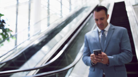 Businessman using mobile mobile phone while moving downstairs on escalator i 4k Live Action