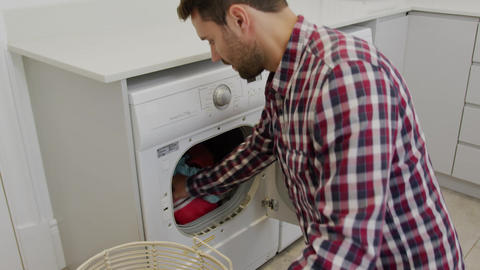 Man removing cloths from washing machine in a comfortable home 4k Live Action