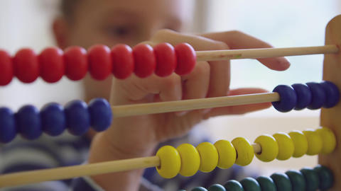 Boy learning mathematics with abacus in a comfortable home 4k Live Action