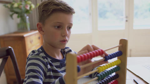Boy learning mathematics on abacus at table in a comfortable home 4k Live Action