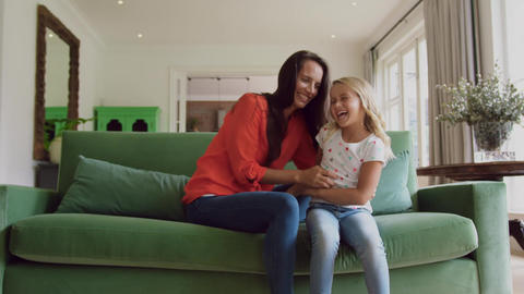 Mother and daughter playing together on sofa at home 4k Live Action