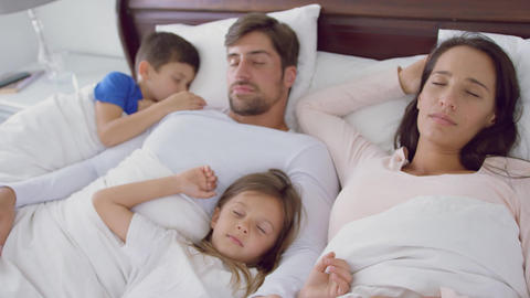 Family sleeping together on bed in bedroom at home 4k Live Action