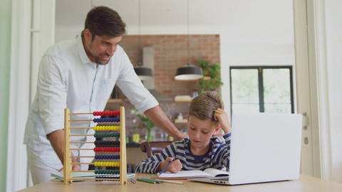 Father helping his son in homework at home 4k Live Action