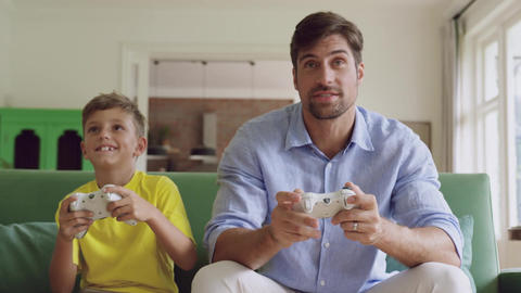 Father and son playing video game together on sofa at home 4k Live Action