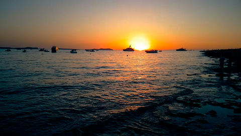 sea wave calm at sunset with sun and boats in horizon, concept of relax and travel of Live Action