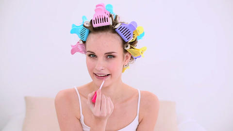 Young model in hair rollers putting on lip gloss Live Action