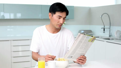 Attractive man eating cereal and reading magazine Live Action