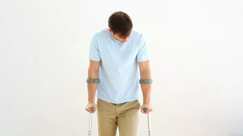 Injured man on crutches stepping towards camera Live Action