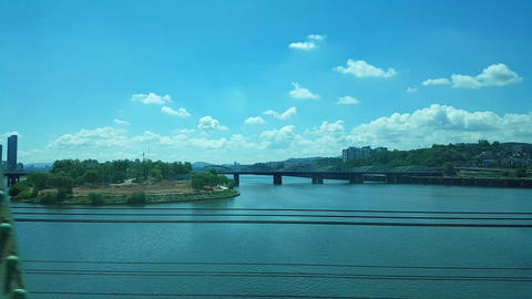 the view outside the window of a subway train passing through the Han River Bridge on a clear day Live Action