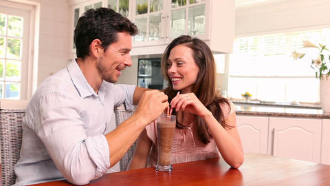 Happy couple drinking a milkshake together Live Action