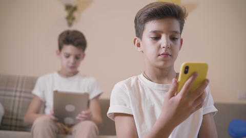 Close-up of Caucasian boy using smart phone as his twin brother sitting at the Live Action