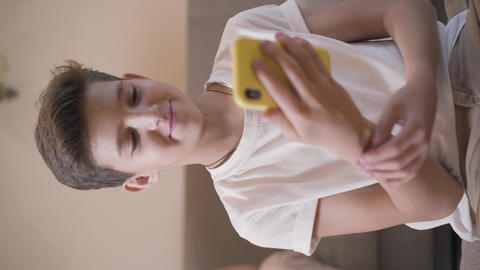 Portrait of Caucasian brunette boy using smart phone. Schoolchild in white T Live Action