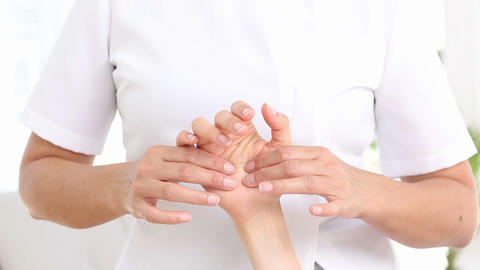 Physiotherapist examining her patients hand Live Action