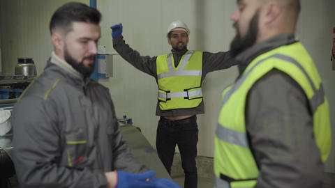 Young Caucasian foreman checking vest on bearded worker. Man in protective Live Action