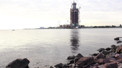 Tilt up from large granite stones on bay bank, tower construction on other side Footage