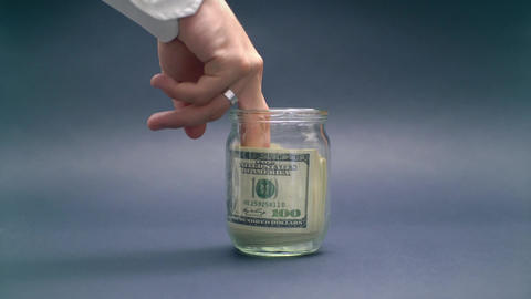 Hand Takes Money from Glass Jar Live Action