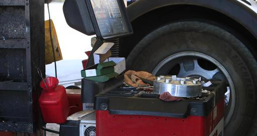 Auto mechanic shop balance wheel on machine DCI 4K Footage