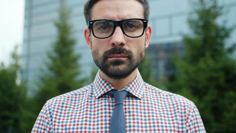 Portrait of handsome bearded guy in glasses wearing shirt and tie outdoors Live Action