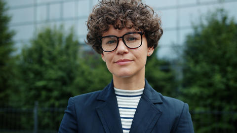 Independent curly-haired lady in glasses standing outside alone wearing suit Live Action