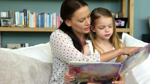 A mother is reading a book to her daughter Live Action