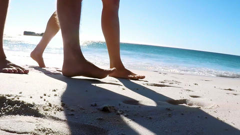 Couple walking together on the beach Live Action