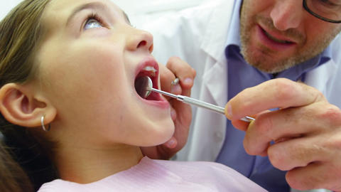 Dentist examining a young patient with dental tools Live Action