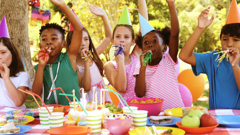 Group of kids blowing party horn while celebrating a birthday Live Action
