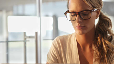 Woman in spectacles sitting in cafe Live Action