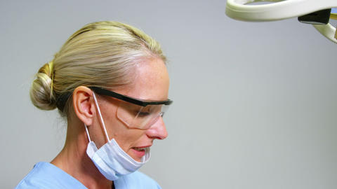 Female dentist assisting male patient to wear virtual reality headset Live Action