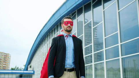 Medium shot of handsome CEO wearing superman cape and mask outside office Live Action