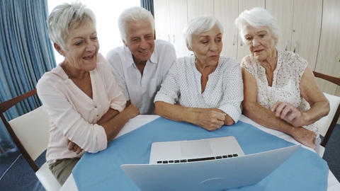 Senior man and woman using laptop in old age home Live Action