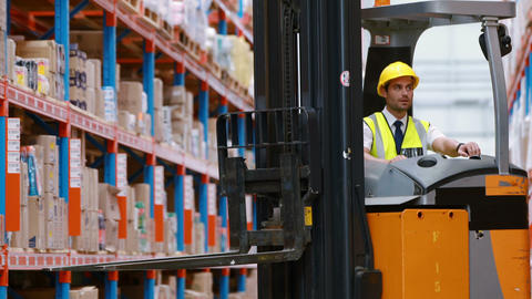 Male warehouse worker using forklift truck Live Action