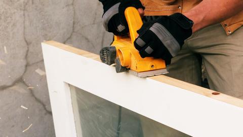 Carpenter polishing a wooden frame Live Action