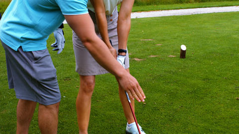 Male instructor assisting woman in learning golf Live Action