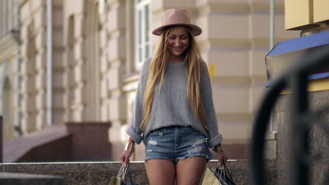 Woman with shopping bags walking on city street Footage