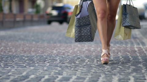 Young woman with shopping bags walking city street Footage