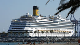 Cruise ship about to leave docked in the port with people on beach Footage