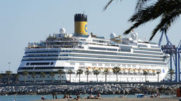 Cruise ship about to leave docked in the port with people on beach and industria Footage