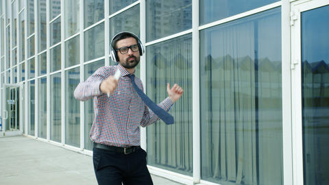 Slow motion of cheerful entrepreneur dancing outdoors wearing headphones Live Action
