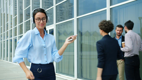 Cheerful business lady dancing outside office center in street wearing Live Action