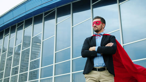 Portrait of handsome businessman in suit wearing superman costume outdoors Live Action