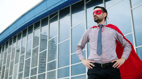 Portrait of ambitious man wearing red superhero mask and cape standing outdoors Live Action