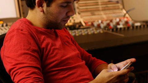 Male audio engineers text messaging on mobile phone Live Action