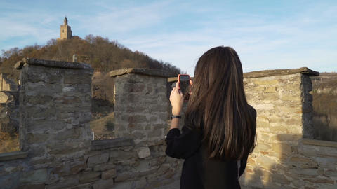 Girl with long brown hair enjoying vacation in Tsarevets, Veliko Tarnovo. Taking Live Action