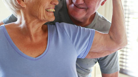 Happy senior couple romancing in bedroom Live Action