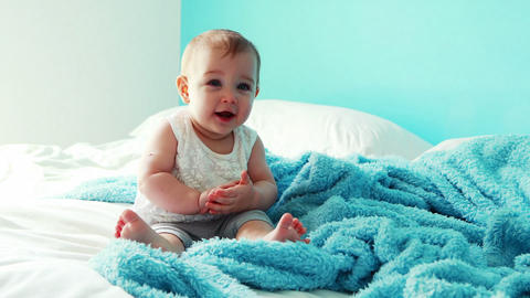 Playful baby girl sitting on bed Live Action