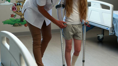 Female doctor assisting girl to walk with crutches Live Action