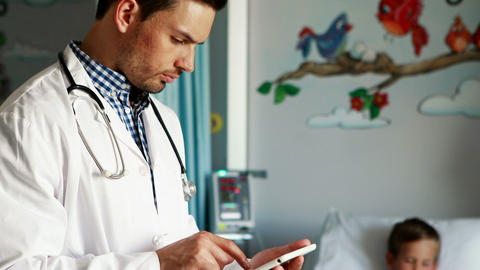 Male doctor using digital tablet during visit in ward Live Action