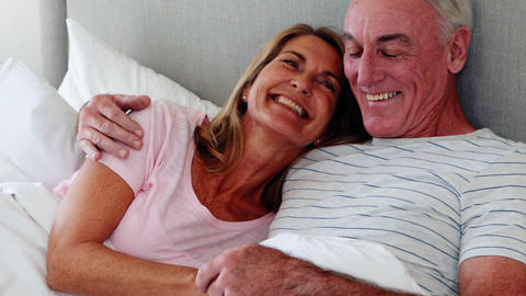 Senior couple embracing on bed Live Action